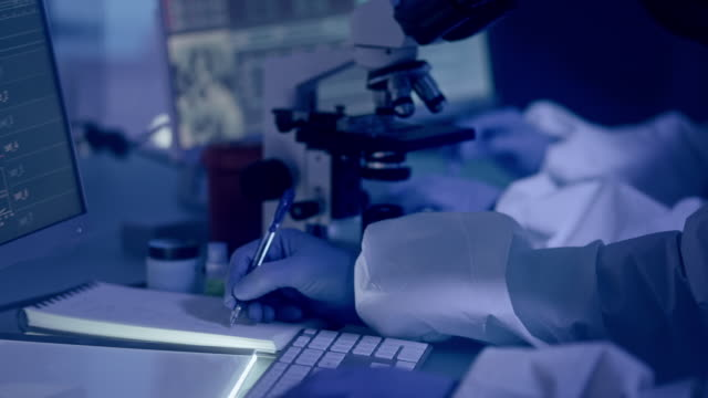 scientists in laboratory working with biohazardous substance. making notes - illustrazione biomedica video stock e b–roll