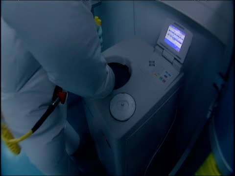 Scientists in protective suits work in airtight virus research laboratory