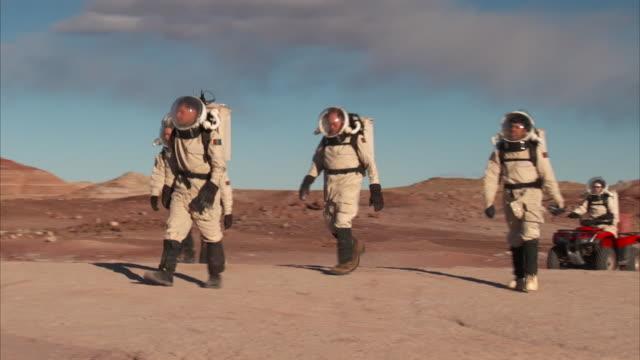 scientists in space-like suits traverse across a barren landscape. - 宇宙服点の映像素材/bロール