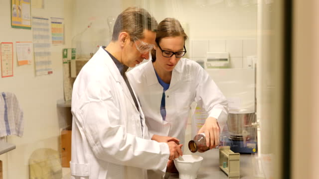 scientists making medicine at pharmacy - mortar and pestle stock videos and b-roll footage