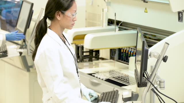 Scientists operating equipment in bio-medical laboratory