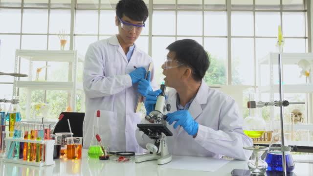 vídeos de stock e filmes b-roll de scientists or biologist work in research laboratory, panning shot - vacina
