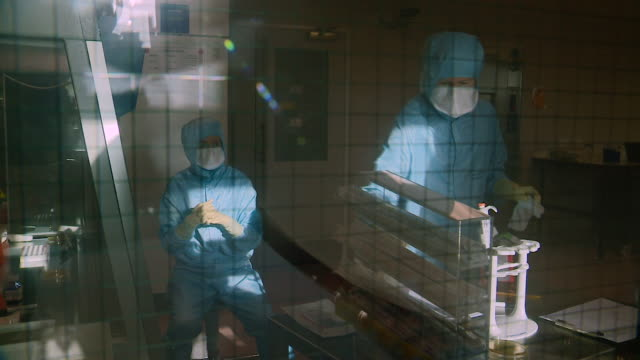 scientists researching vaccines for mers work wear protective clothing and masks as they work behind screens at the clinical biomanufacturing... - colleague stock videos & royalty-free footage