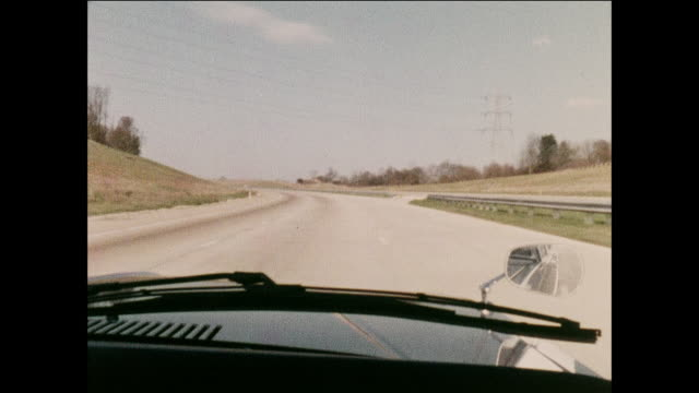 vídeos de stock, filmes e b-roll de pov scientists simulate the thoughts of a tired drivers brain / truck in lane recedes past windshield on highway / highway ahead approaches windshield / scientists look sideways / car traffic in lane ahead approaches windshield - foco difuso