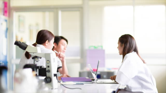 Scientists Sitting Around Table Having Meeting