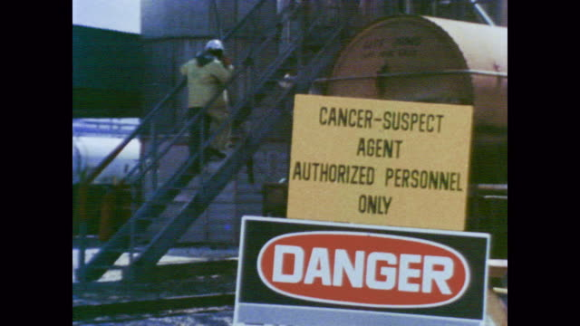 1978 scientists test chemicals in the lab as chemical plant workers interact with carcinogenic materials - 化学薬品点の映像素材/bロール