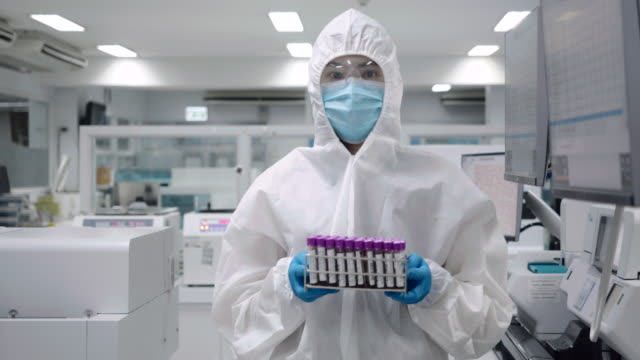 scientists walking and wear protective clothing holding a blood test tube in the sterile room in the laboratory. - laboratory equipment stock videos & royalty-free footage