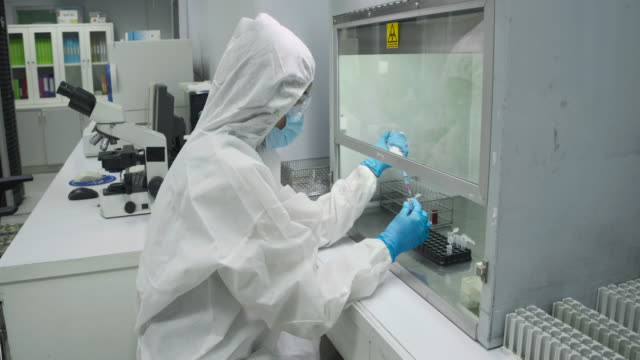 scientists wear protective clothing in the sterile room and using the pipette in the experiment - chemistry stock videos & royalty-free footage
