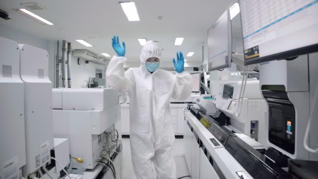 vídeos y material grabado en eventos de stock de los científicos usan ropa protectora caminar y bailar con placer después de un trabajo exitoso en la sala estéril en el laboratorio. - viernes