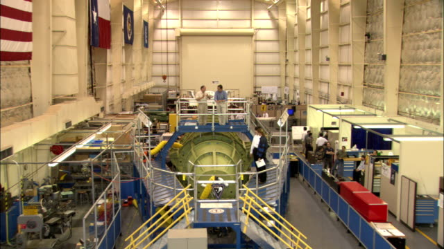 nasa scientists work in a large research room containing a mock-up of the x-38 crew return vehicle. - アメリカ航空宇宙局点の映像素材/bロール