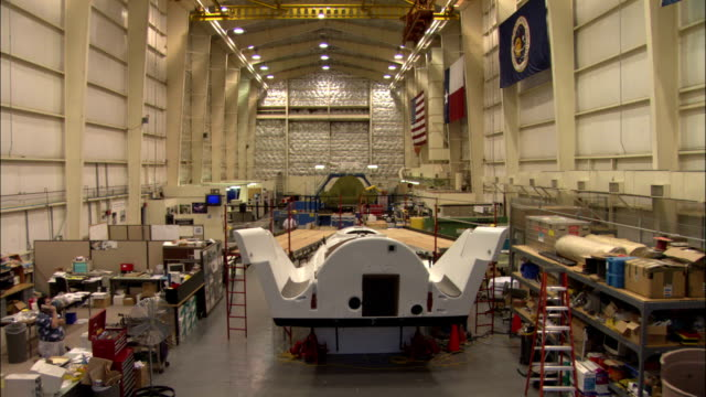 nasa scientists work in a large research room containing a mock-up of the x-38 crew return vehicle. - nasa video stock e b–roll