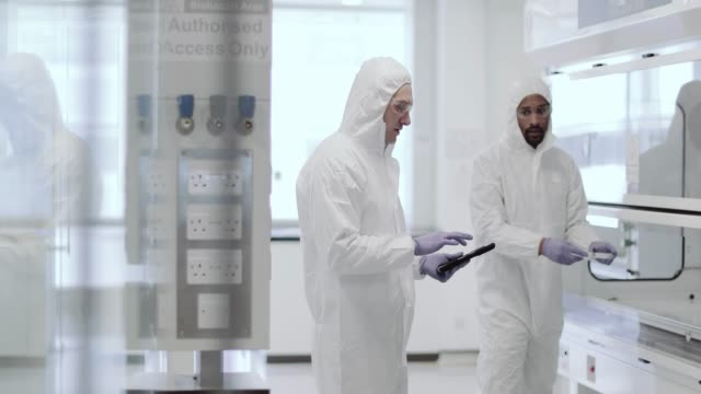 stockvideo's en b-roll-footage met scientists working in a biohazard area lab - microbiologie