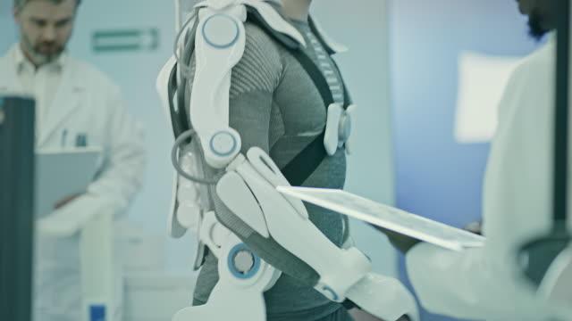 scienziati che lavorano al progetto di esoscheletro alimentato in laboratorio. - human spine video stock e b–roll