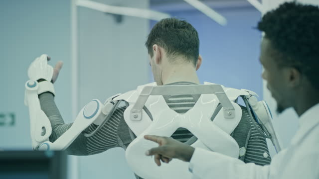scientists working on powered exoskeleton project in lab. - exoskeleton stock videos & royalty-free footage