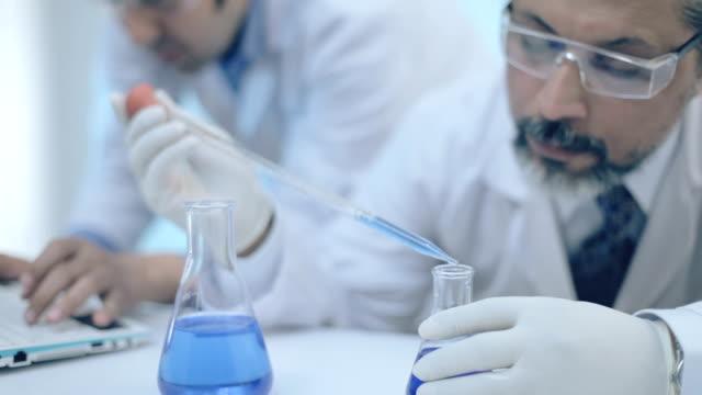vídeos de stock, filmes e b-roll de cientistas que trabalham com produtos químicos em um laboratório. - experimento