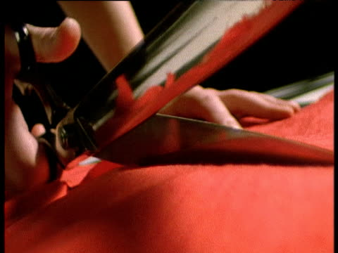 scissors cutting red cloth towards camera - cucire video stock e b–roll