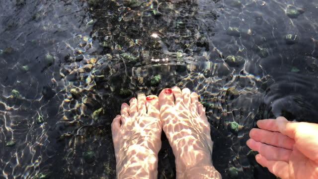 足湯に浸りながら、手で温泉水をすくい上げる - barefoot点の映像素材/bロール