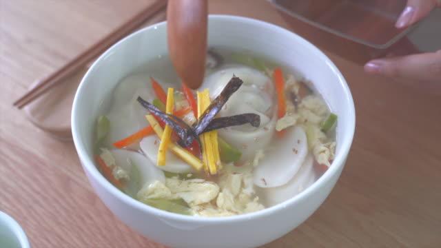 scooping a dumpling from tteok mandu guk (korean rice cake soup with dumplings) - korean new year stock videos & royalty-free footage