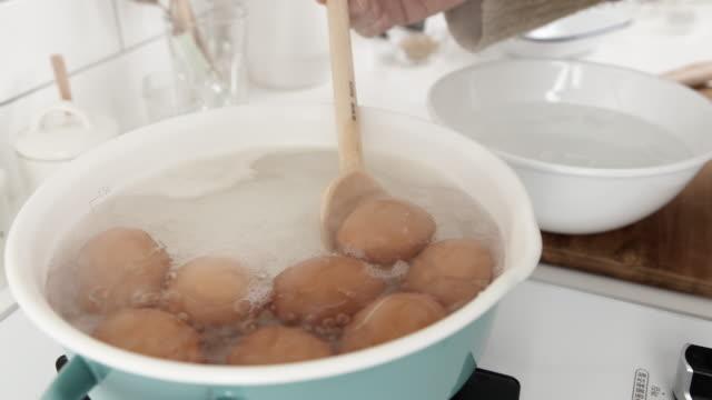 vídeos y material grabado en eventos de stock de scooping eggs from a pot on a gas stove - hervido