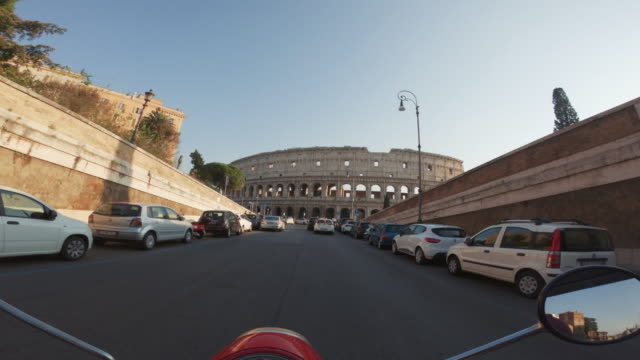 pov scooter: on the motorbike by the coliseum of rome - motorino video stock e b–roll