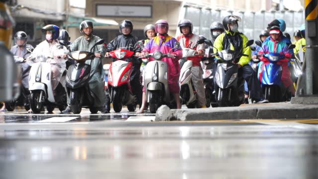 vidéos et rushes de cavaliers de scooter attendant sous la pluie - taipei