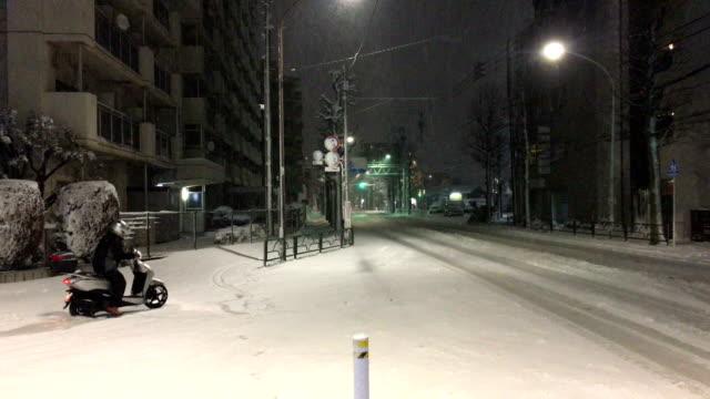 Scooter struggles on slick road after winter storm dumps heavy snow on Tokyo