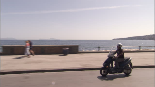 a scooter travels the coastal highway along the gulf of naples - motorroller stock-videos und b-roll-filmmaterial