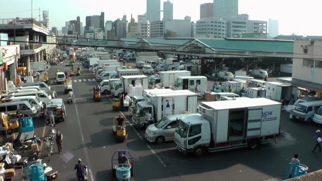 Scooters and tow motors zip around trucks at the Tsukiji Market.