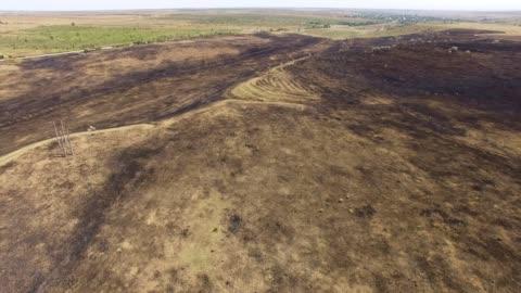 vidéos et rushes de antenne: la terre brûlée dans le champ après incendie - sol phénomène naturel