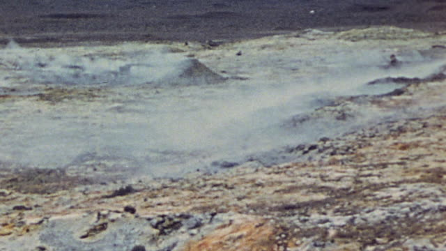 vídeos de stock, filmes e b-roll de pan scorched earth still smoking and melted slag in a shell hole with two soldiers examining the area / iwo jima japan - batalha de iwo jima