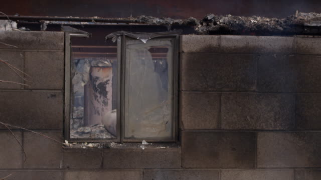 scorched water heater seen through a broken window behind drifting smoke - burnt stock videos & royalty-free footage