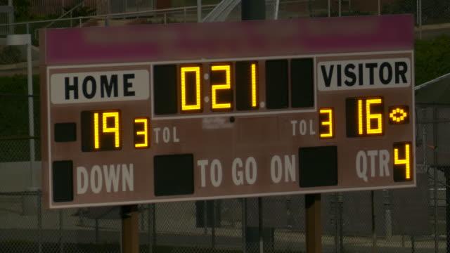 scoreboard at a night football game stadium, friday night lights, american football. - scoreboard stock videos & royalty-free footage