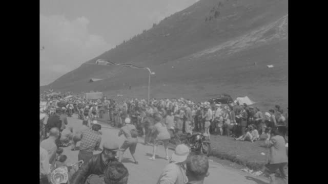 scores of bicyclists on picturesque country road / riding behind three riders / chef with cigarette applauding / group of participants and motorcycle... - tour de france stock-videos und b-roll-filmmaterial