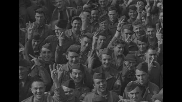 vídeos de stock, filmes e b-roll de scores of british and americans give v for victory signs from deck of transport ship / british naval officers and single american on bridge of ship... - oficial posto militar