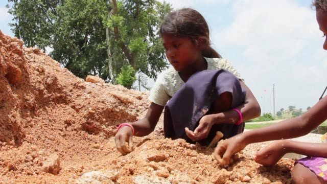 scores of children risk their lives daily as they toil in illegal mines to extract mica flakes a shimmery ingredient used globally in makeup products... - schist stock videos and b-roll footage