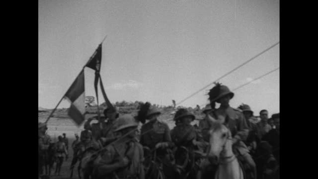 Scores of Ethiopian and Italian soldiers marching in desert / Italian officers on horses pass and stop near Italian flag / the men pass thatched roof...