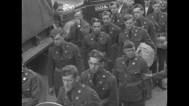 scores of men at staging area boarding trucks / lines of men and a sousaphone being loaded / vs pov several trucks of men cheering and waving at the... - seconda guerra mondiale video stock e b–roll