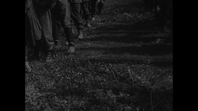 vídeos de stock, filmes e b-roll de vs scores of polish prisoners of war stand field with smoke behind them bedraggled men look at camera with pan down to their muddy shoes the men... - polônia
