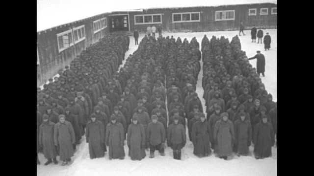 vs scores of russian prisoners stand in formation in a prison camp and moving en masse away from camera with barbed wire fence just beyond they stand... - prison camp stock videos & royalty-free footage