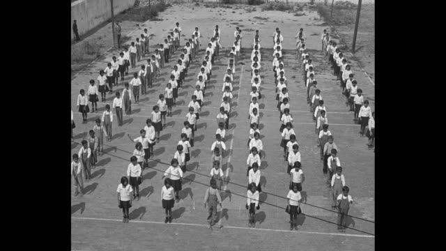 scores of uniformed kids perform calisthenics by raising, lowering arms and turning their bodies in unison / note: exact month/day not known - lowering stock videos & royalty-free footage
