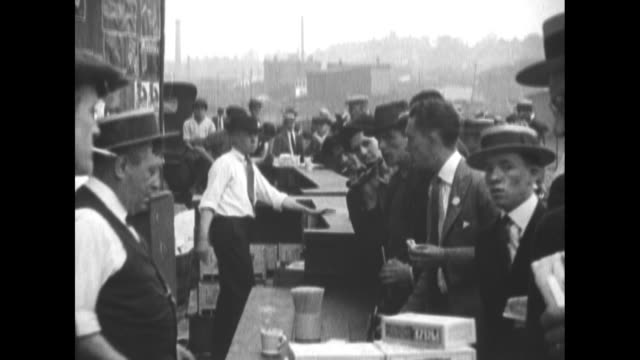 """stockvideo's en b-roll-footage met scores of vendors and men in straw boaters; men underneath signs """"bleachers $5.50"""" & """"police station"""" / vendors briskly selling beverages / the huge... - bioscoopjournaal"""