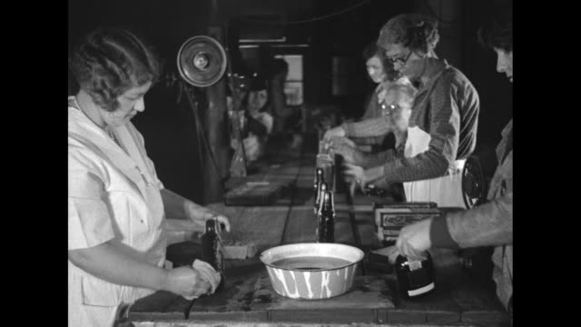 stockvideo's en b-roll-footage met scores of whiskey bottles stand on tables in factory as women examine bottles moving on slow conveyor belt / women wipe off sealed bottles with damp... - lopende band