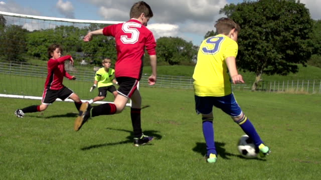 scoring goal in kid's football / soccer game - taking a shot sport stock videos & royalty-free footage