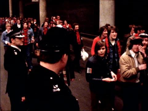 vídeos y material grabado en eventos de stock de scotland fan stabbed to death on train england london ext shots of crowds of scottish football supporters along at train station past lines of police... - música pop