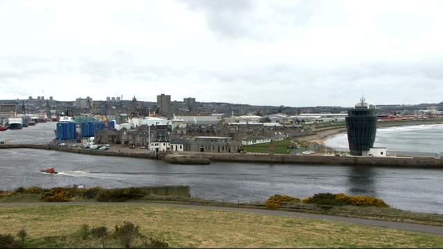 general views of aberdeen / workers on oil plant; general view ships moored in harbour / small speed boat sailing along, general view of habour /... - aberdeen schottland stock-videos und b-roll-filmmaterial