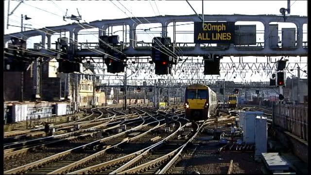 signal workers to stage threeday strike from christmas eve scotland ext train along tracks close shot of red light train away past another railway... - railway signal stock videos & royalty-free footage