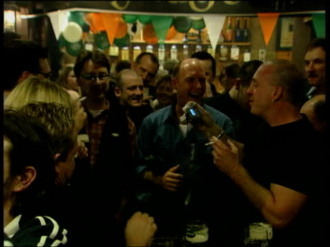 smoking ban in public places comes into force date man with guitar speaking into microphone in pub people stubbing out cigarettes - zigarettenstummel stock-videos und b-roll-filmmaterial