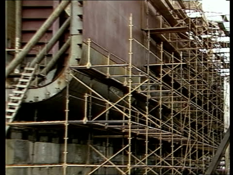 scott lithgow; c4n scotland: clydeside: greenock gv huge crane in scott lithgow shipyard zoom to oil platform under construction unfinished britoil... - zoom in点の映像素材/bロール