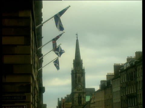 scottish and union jack flags blow in wind church spire in background edinburgh - edinburgh scotland stock videos & royalty-free footage