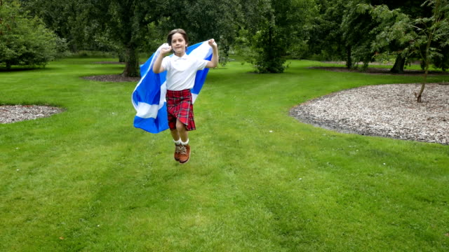scottish boy in kilt running with the flag on the meadow - scottish flag stock videos & royalty-free footage